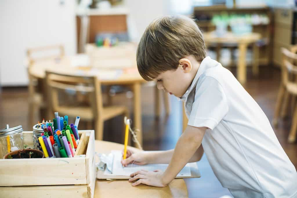 Creation Village preparatory student writing at table with pencil